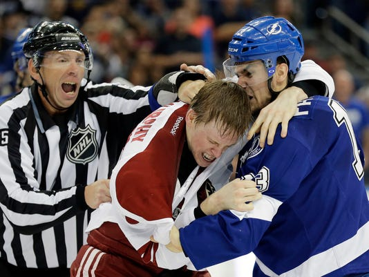 Linesman Pierre Racicot, left, tries to break up a fight by Tampa Bay Lightning center Cedric Paquette, right, and Arizona Coyotes defenseman Connor Murphy during the second period of an NHL hockey game Tuesday, Oct. 28, 2014, in Tampa, Fla. (AP Photo/Chris O'Meara)