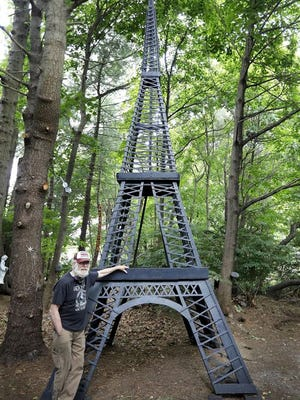 Steve Temple with the wooden replica of the Eiffel Tower that he built in the backyard of his Abington home.