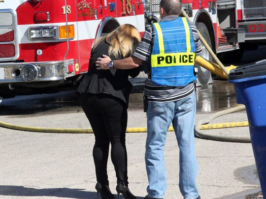 A woman is helped outside a home that caught fire Tuesday