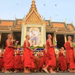 Cambodian Buddhist monks walk past a portrait of King Norodom Sihamoni as they attend the Visak Bochea Day celebrations in Phnom Penh, Cambodia, May 20, 2016.