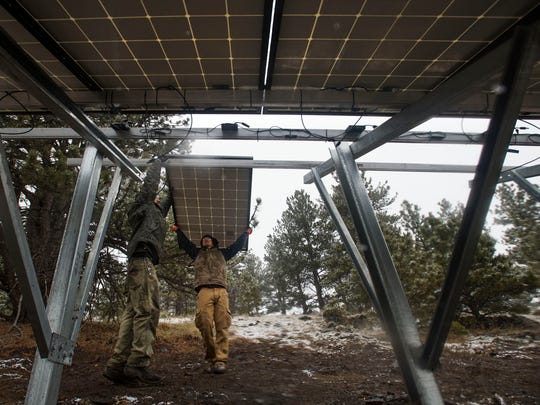 NamastŽ Solar installers Houston Sherer, left, and Davis Fogerty hoist a module onto the framework of a ground mount solar panel system during an install on Wednesday, March 28, 2018, in Bellvue, Colo.