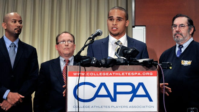 Northwestern quarterback Kain Colter second from right, speaks while College Athletes Players Association president Ramogi Huma left, United Steel Workers National Political Director Tim Waters second from left, and United Steel Workers president Leo Gerard right, look on during a news conference in Chicago, Tuesday, Jan. 28, 2014.
