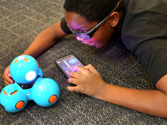 Austin Bilbro, 9, works on a dash and dot coded robot,