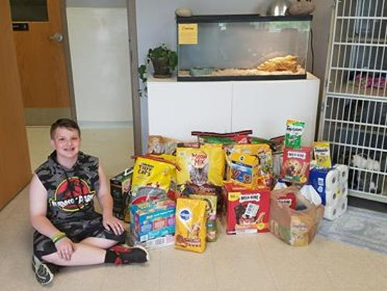 Christian Edwards, 11, poses with supplies he donated