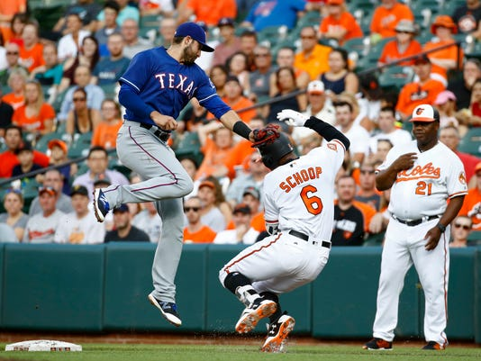 Texas Rangers first baseman Joey Gallo, left, misses the tag on Baltimore Orioles' Jonathan Schoop as Schoop slides safely into first in the first inning of a baseball game in Baltimore, Wednesday, July 19, 2017. (AP Photo/Patrick Semansky)