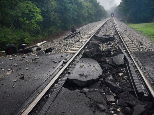 A damaged rail bed is seen near a CSX train after the