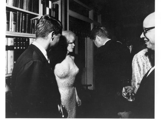 Robert Kennedy, left, and Marilyn Monroe talk with