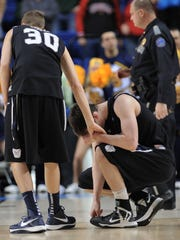 Butler's Andrew Smith is consoled by teammate Emerson Kampen after Smith missed the last shot that would have won the game with a little over two seconds left against Marquette during Saturday's NCAA tournament game at Rupp Arena in Lexington, Kentucky on March 23, 2013. Butler lost 74-72.