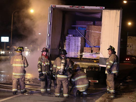 Firefighters work after extinguishing a fire in semi-trailer