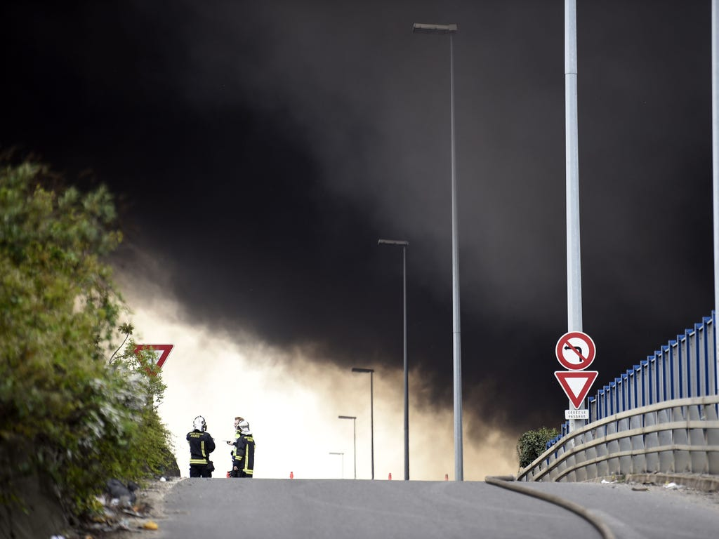 Black smoke rises above the A86 highway in La Courneuve, north of Paris, as firefighters work a nearby warehouse fire on April 17. The fire broke out around midday in a textile and shoe warehouse.