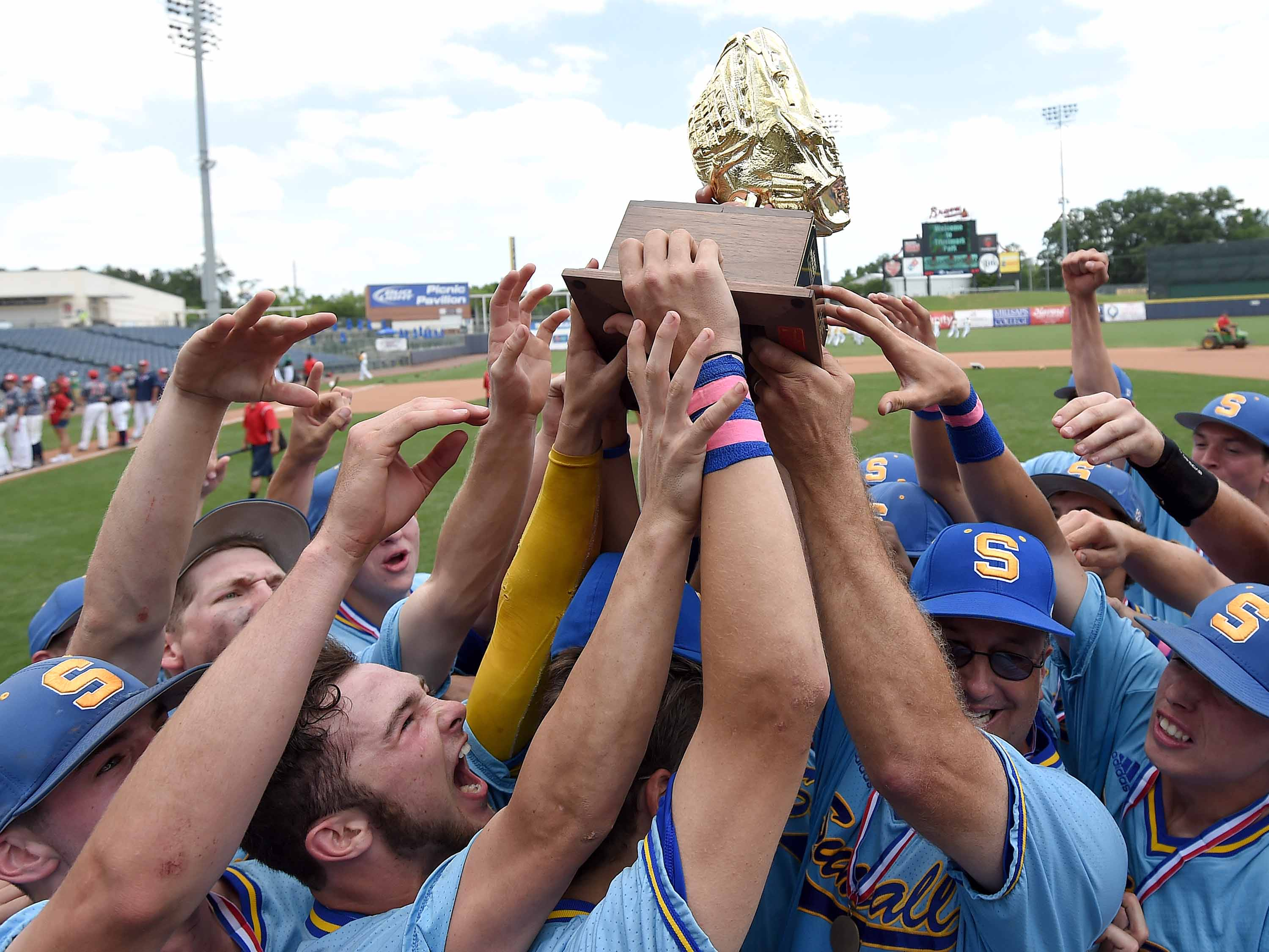 The Sumrall Bobcats celebrate with the Class 3A state championship trophy after beating Belmont 7-2 in game 3 of the State Championshop series Saturday at Pearl.