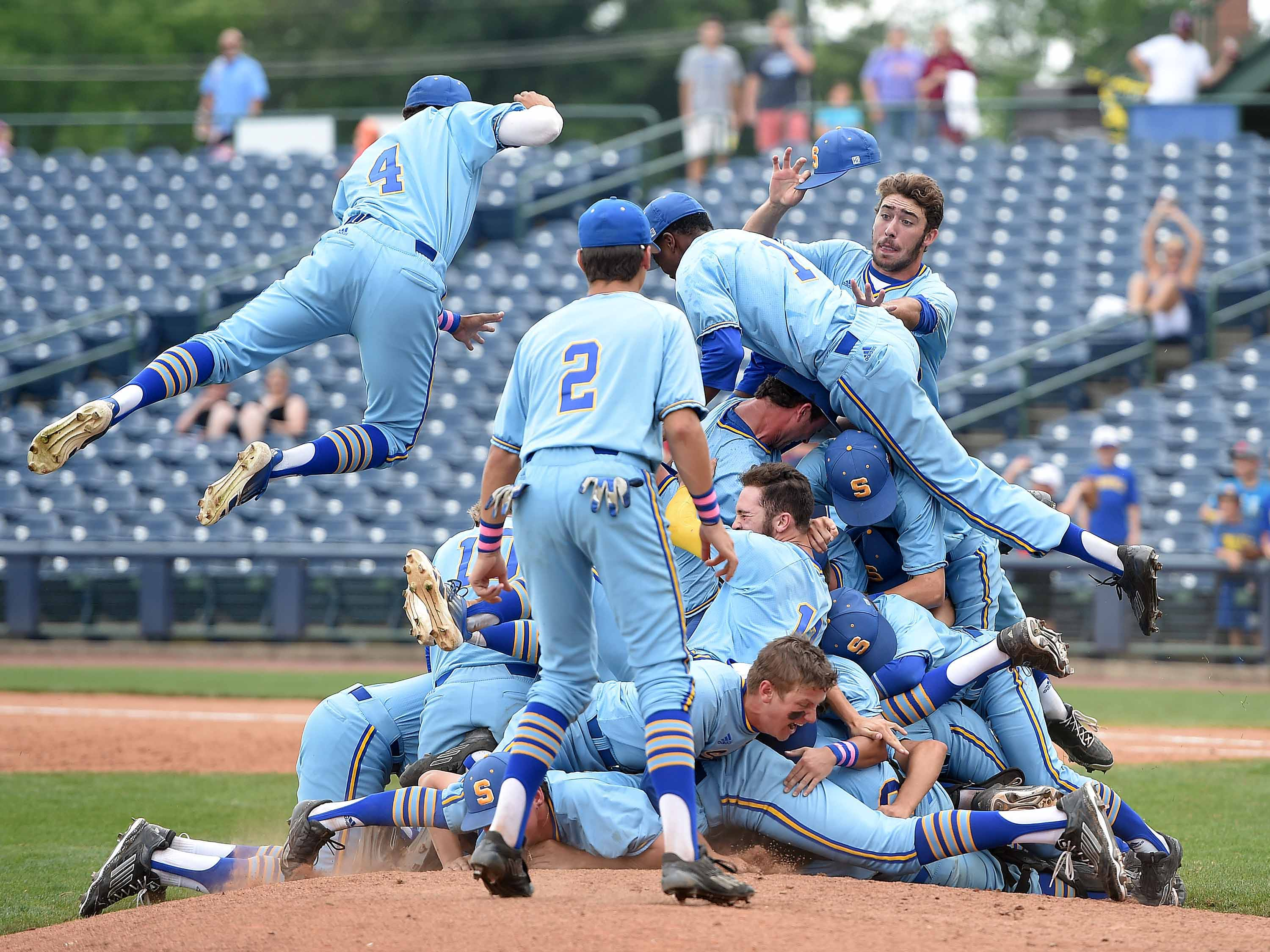 The Sumrall celebration begins with the traditional dog pile near the pitcher's mound after the Bobcats beat Belmont 7-2 in Game 3 on Saturday, the final day of the 2015 MHSAA Baseball State Championships at Trustmark Park in Pearl.