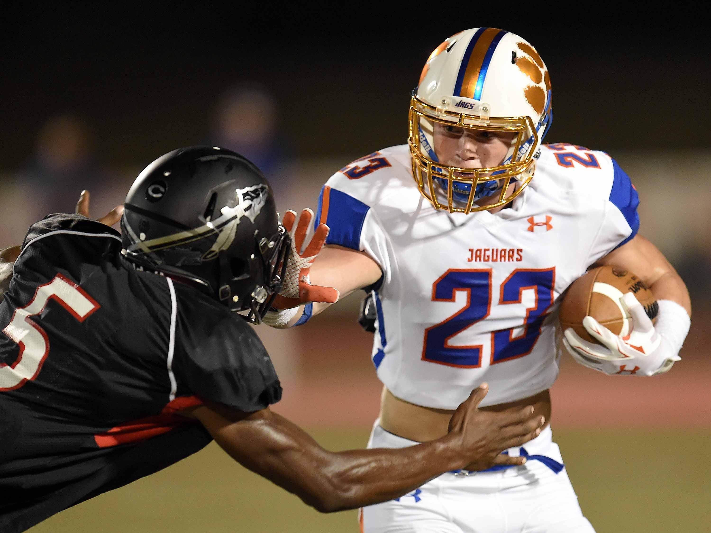 Madison Central's Will Brooks (23) stiff arm's Clinton's Cam Akers on Friday, September 25, 2015, at Clinton High School in Clinton, Mississippi.