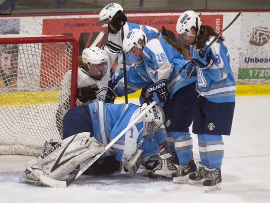 A trio of South Burlington defenders line up to protect goalie Erin Church (1) as she covers up a puck in the crease during the first period of Saturday's game against Rice at Cairns Arena.