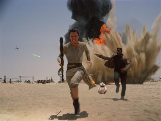 """Daisey Ridley as Rey, left, and John Boyega as Finn are seen in """"Star Wars: The Force Awakens."""""""