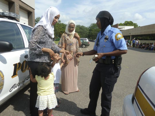 This undated photo shows Kadra Mohamed hands out police badge stickers at a community event attended by Somali families in St. Paul. Minn. Police departments are relaxing traditional grooming standards and getting away from rules that used to require a uniformly clean-shaven, 1950s look. That's because there's a national hiring crisis and departments are seeking a more diverse applicant pool That means more officers are on the job with tattoos inked on their forearms, beards on their chins, or religious head coverings like hijabs and turbans in place of (or tucked beneath) their blue caps. (John M. Glionna/Los Angeles Times via AP)