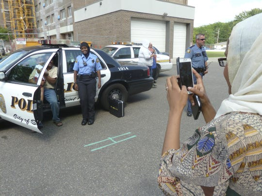 This undated photo shows Kadra Mohamed posing for pictures taken by a Somali woman at community event in St. Paul Minn. Police departments are relaxing traditional grooming standards and getting away from rules that used to require a uniformly clean-shaven, 1950s look. That's because there's a national hiring crisis and departments are seeking a more diverse applicant pool That means more officers are on the job with tattoos inked on their forearms, beards on their chins, or religious head coverings like hijabs and turbans in place of (or tucked beneath) their blue caps. (John M. Glionna/Los Angeles Times via AP)