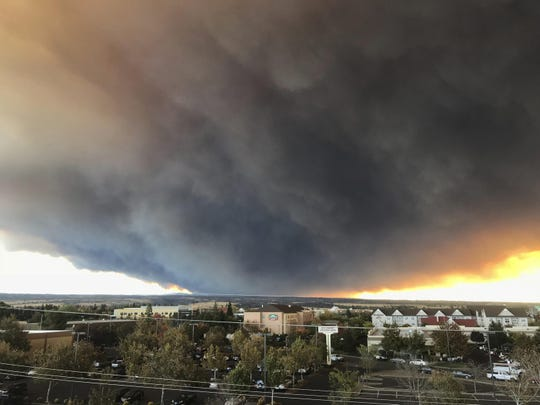The massive plume from the Camp Fire, burning in the Feather River Canyon near Paradise, Calif., wafts over the Sacramento Valley as seen from Chico, Calif., on Thursday, Nov. 8, 2018. Authorities in Northern California have ordered mandatory evacuations in a rural area where the wildfire has grown to 1,000 acres (405 hectares) amid hot and windy weather.