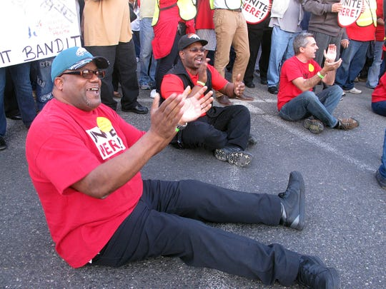 Casino workers sit in the roadway as they occupy an intersection and block traffic in Atlantic City N.J. on Wednesday Oct. 8, 2014. They were protesting givebacks demanded by the owners of the Trump Taj Mahal Casino Resort in return for keeping the casino open. The company wants to eliminate employee health care and pension plans. Twenty four of the workers were arrested in the protest. (AP Photo/Wayne Parry)