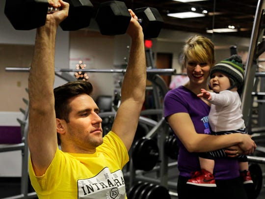 Curt Isenbarger, 29, of Lafayette lifts weights at the downtown YMCA on New Year's Eve while his wife Vanessa and their son, Ian, watch. The Isenbargers are committed to making fitness a part of their family for the new year and beyond.