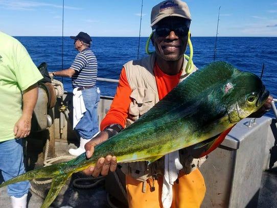 An angler holds a mahi-mahi landed on the 125-foot