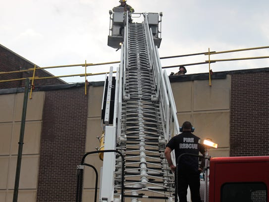 Marion City Firefighter spray down flames on top of the public health building Friday. The blaze is believed to have started after a piece of roofing material hit an electrical service drop.