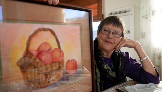 Artist Lorraine Dooner displays one of her water colors at her home.