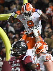 Clemson running back Travis Etienne (9) is lifted after