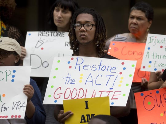 Dahjour Croson, 17, of Roanoke, and a member of the youth NAACP council, protests outside of U.S. Rep. Bob Goodlate's regional office with others calling for the restoration of provisions of the Voting Rights Act of 1965, on Monday, Aug. 8, 2016, in Roanoke, Va. (Erica Yoon/The Roanoke Times via AP)
