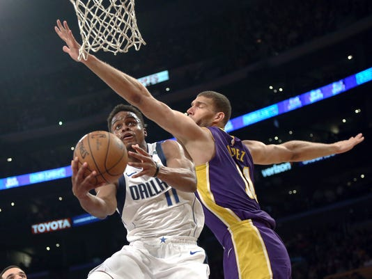 Dallas Mavericks guard Yogi Ferrell (11) attempts a shot as Los Angeles Lakers center Brook Lopez (11) defends during the first half of an NBA basketball game in Los Angeles on Wednesday, March 28, 2018. (AP Photo/Reed Saxon)