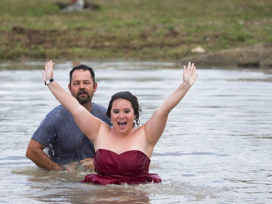 Eddie Chesser and Erica Flesher, the Swamp Buggy Queen, jump into the water after Chesser won during the Swamp Buggy Races on Saturday, March 25, 2017 at Florida Sports Park in East Naples.