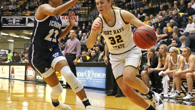 Fort Hays State University's Whitney Randall drives toward the basket against Washburn's Hunter Bentley during a game last season at Gross Memorial Coliseum in Hays. The TIgers will open the season against Washburn at home on Thursday.