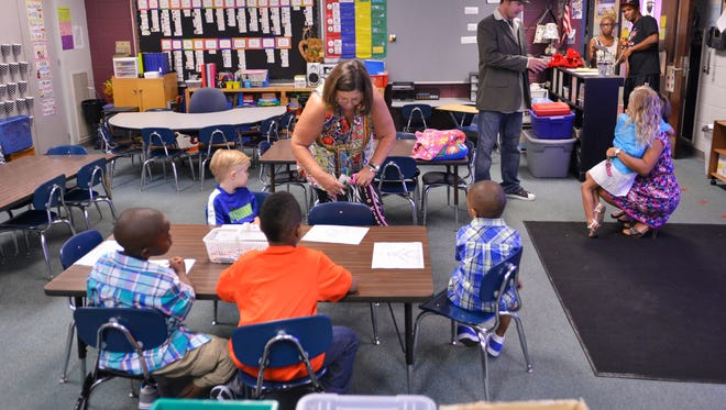 Tonya Hibbard, kindergarten teacher, puts a child's backpack on their chair as the first day of classes get underway at  Wetumpka Elementary School on Monday, Aug. 4, 2014.