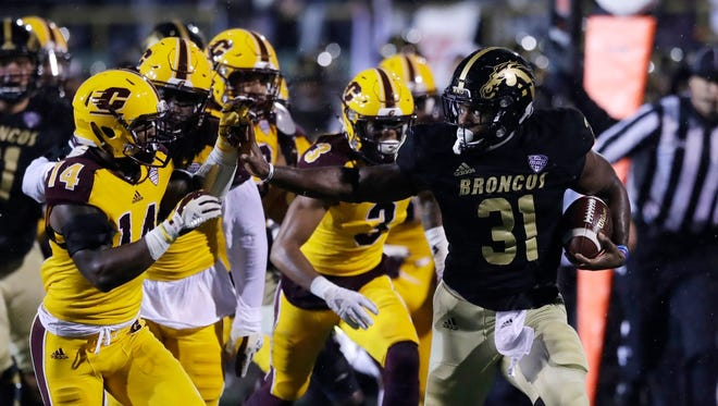 Western Michigan running back Jarvion Franklin is chased on the sidelines by Central Michigan defensive back Josh Cox (14) during the first half of an NCAA college football game, Wednesday, Nov. 1, 2017, in Kalamazoo, Mich.