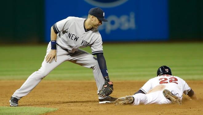 The Indians' Jason Kipnis  dives safely into second base on a steal as Yankees shortstop Derek Jeter applies a late in the eighth inning of  Thursday night's game in Cleveland.
