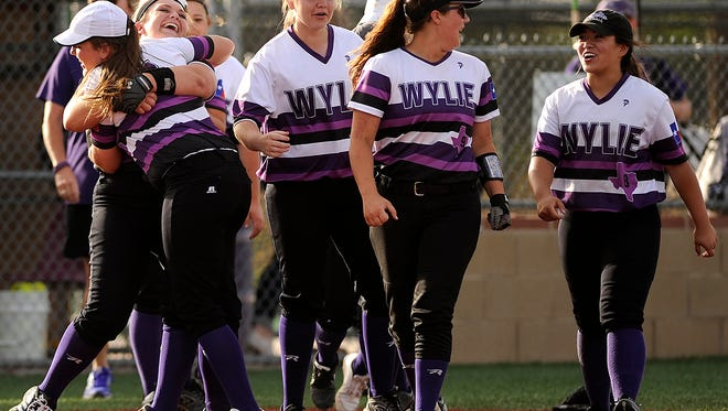 Wylie pitcher Kamwren Jackson (10) gets a hug from teammate Bailey Buck (4) after the Lady Bulldogs' 8-7 win on Tuesday, April 4, 2017, at Wylie High School.