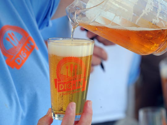 A volunteer pours a glass of beer from Sun King during the 4th Dig IN, a celebration where local chefs, restaurants and brewers come together in White River State Park, 2013.