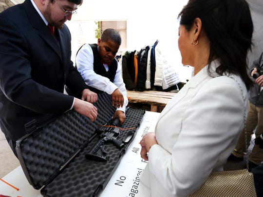 A woman has her weapon checked for being unloaded and zip-tied at the World Peace and Unification Sanctuary, Wednesday Feb. 28, 2018 in Newfoundland, Pa. Worshippers clutching AR-15 rifles participated in a commitment ceremony at the Pennsylvania-based church. The event Wednesday morning led a nearby school to cancel classes for the day. The church's leader, the Rev. Sean Moon, said in a prayer that God gave people the right to bear arms.