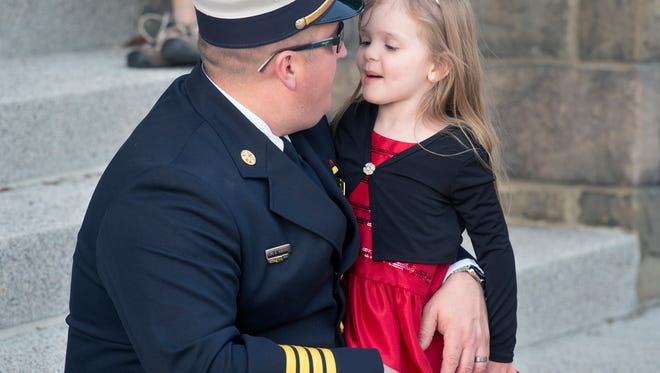 Deputy chief Chadd Deardorff has a moment with his daughter Sophia, age 4, before the 140th Annual Memorial Service of the York City Department of Fire/Rescue Services