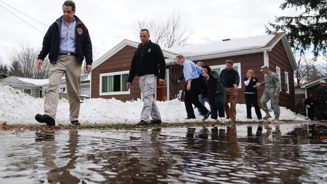 New York Gov. Andrew Cuomo, left, walks along a watery driveway while surveying the aftermath of last week's lake-effect snowstorms on Monday, Nov. 24, 2014, in West Seneca, N.Y.