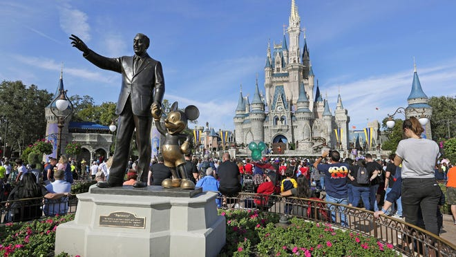 In this Jan. 9, 2019 photo, guests watch a show near a statue of Walt Disney and Micky Mouse in front of the Cinderella Castle at the Magic Kingdom at Walt Disney World in Lake Buena Vista, part of the Orlando area in Fla. Officials from SeaWorld and Disney World say they hope to open their theme parks in Orlando, Florida, in June and July. A city task force approved the plans on Wednesday.