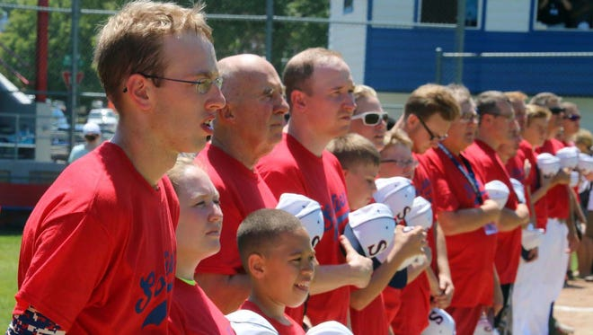Caleb Kvale, left, and members of the Sorlien family baseball team hold their caps to their hearts during the National Anthem.