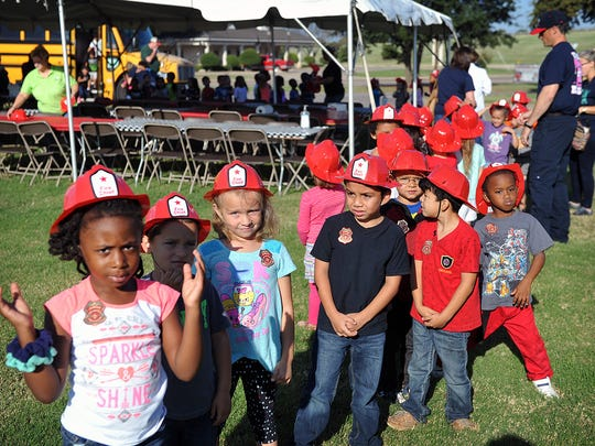 Kindergartners from Lamar Elementary each received a red plastic fire helmet and sticker badges during a field trip Friday to learn about fire safety. First National Bank hosted the event and served hamburgers later.