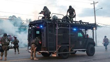 A photo made available on 12 August 2014 shows St. Louis County Tactical Police officers firing tear gas along West Florissant Road near St. Louis, Missouri, two days after a St. Louis county police officer reportedly shot and killed unarmed 18-year-old Michael Brown in Ferguson, Missouri