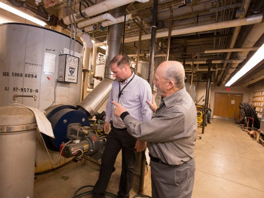Bob McGreevy (right), Co-founder of EffectivEnergy Solutions, shows Todd Amiet (left), Director of Buildings and Grounds for the South Brunswick School District, the new boilers and water tanks in the basement of the South Brunswick High School.