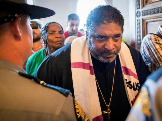 The Rev. William Barber argues wit troopers at state capitol in Frankfort, Kentucky