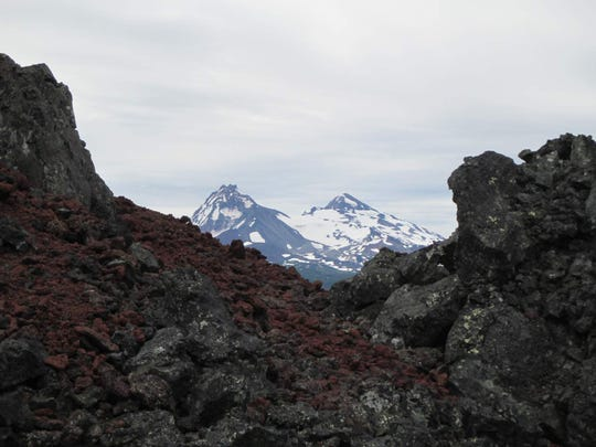 North and Middle Sister appear between the lava rock near the top of Little Belknap Crater.