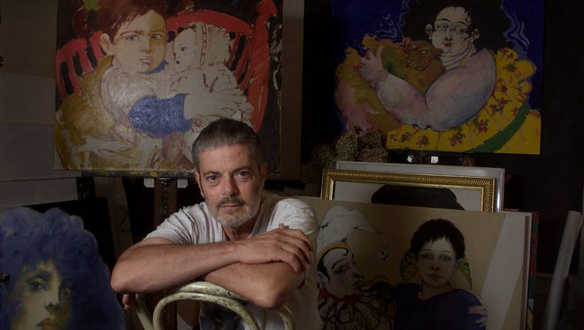 Rochester artist Ramon Santiago sits in his Rochester studio Thursday, August 16, 2001, surrounded by works of his art.