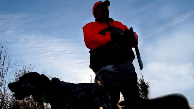 A photo illustration of a hunter and hunting dogs.