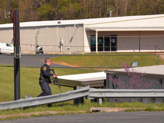 A Virginia State Trooper creates a perimeter with other